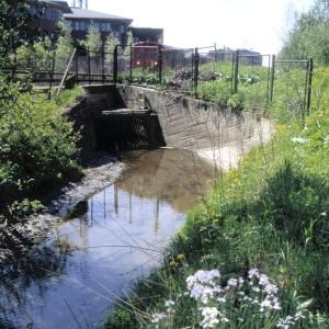 47 Hovinbekken forsvinner i kulvert  under T-banen på Risløkka